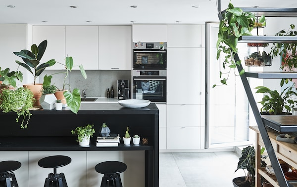 A monochrome kitchen and dining area with open staircase.