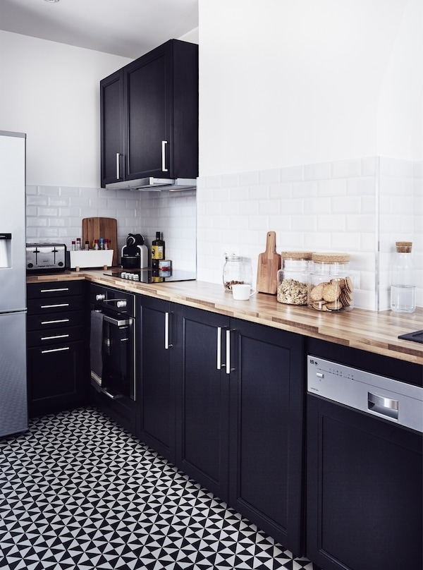 A monochrome kitchen with white walls, black cabinets, and a black and white tiled floor.