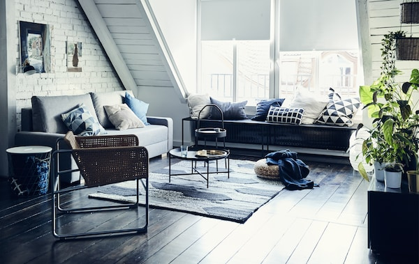 A monochrome living room with a pitched roof, grey sofa, rattan armchair and large textured rug.