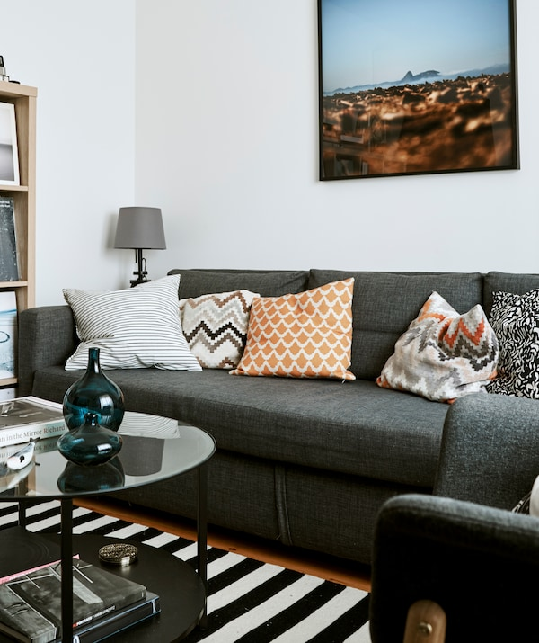 A monochrome living room with grey sofa, black and white striped rug, a round black and glass coffee table.