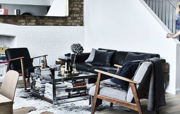 A monochrome living room with two IKEA armchairs and a black sofa.