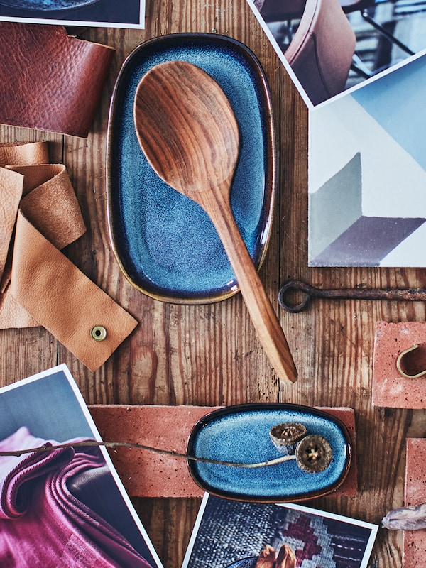 A moodboard of a wooden spoon, an oval dish, photographs, pieces of leather and fabric, hooks and a kitchen tile.