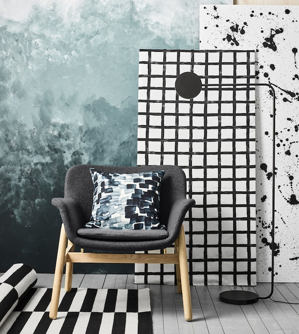 A moodboard with an IKEA VEDBO dark grey armchair, YPPERLIG black floor lamp and textured artwork up against a wall.