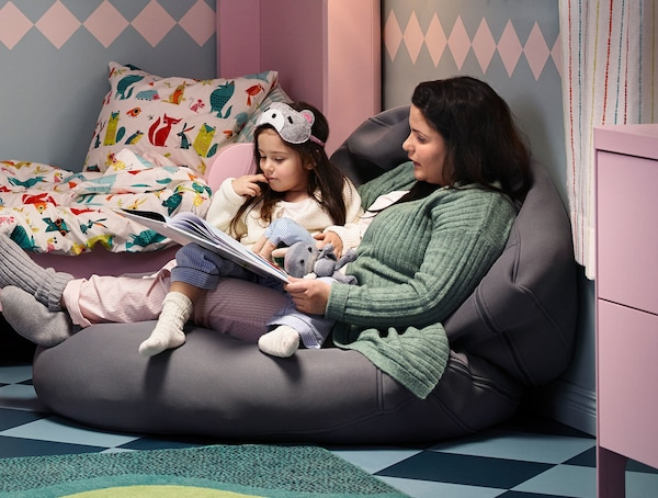 A mother and daughter sitting on a bean bag reading a book.