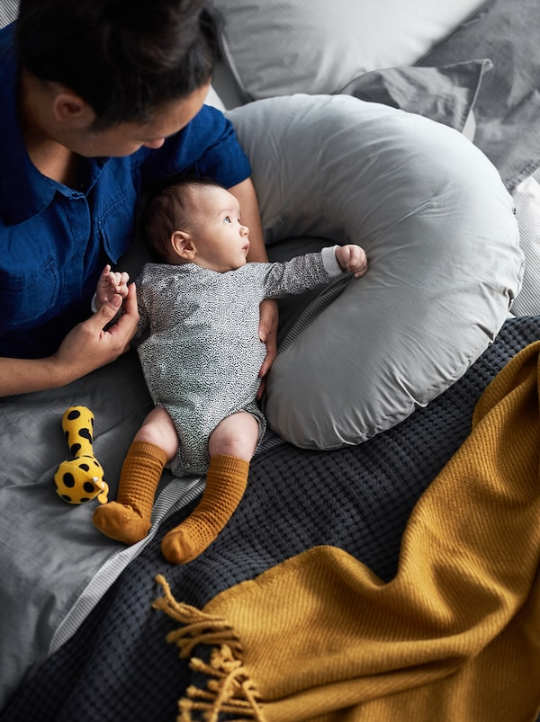 A mother and her baby sitting in a bed with covers in grey and mustard shades, and a nursing pillow beside them.