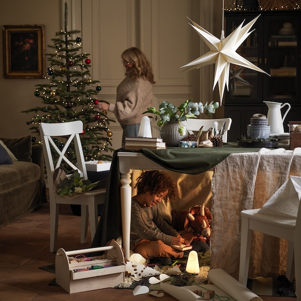 A mother and her child a decorating a room for Christmas.
