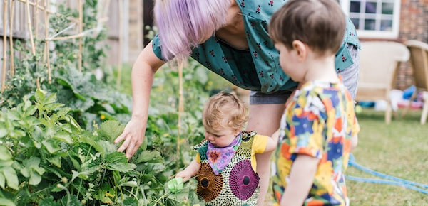 A mother and her two children are standing in their backyard. She is looking at a plant and moving its leaves with her hand.