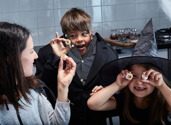 A mother and her two kids dressed in Halloween costumes are playing with their food.