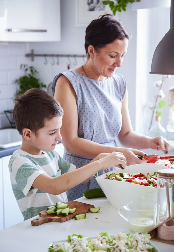 A mother and her young son prepare a salad together in a white kitchen.