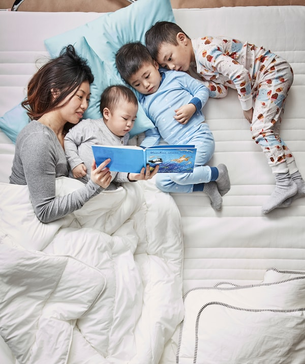 A mother and three children lying in a bed clad with white bedding, reading a story together.