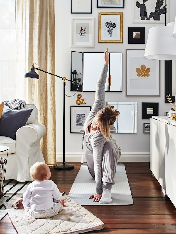 A mother does yoga on a mat in a living room with a lot of pictures on the wall while her baby sits nearby and watches.