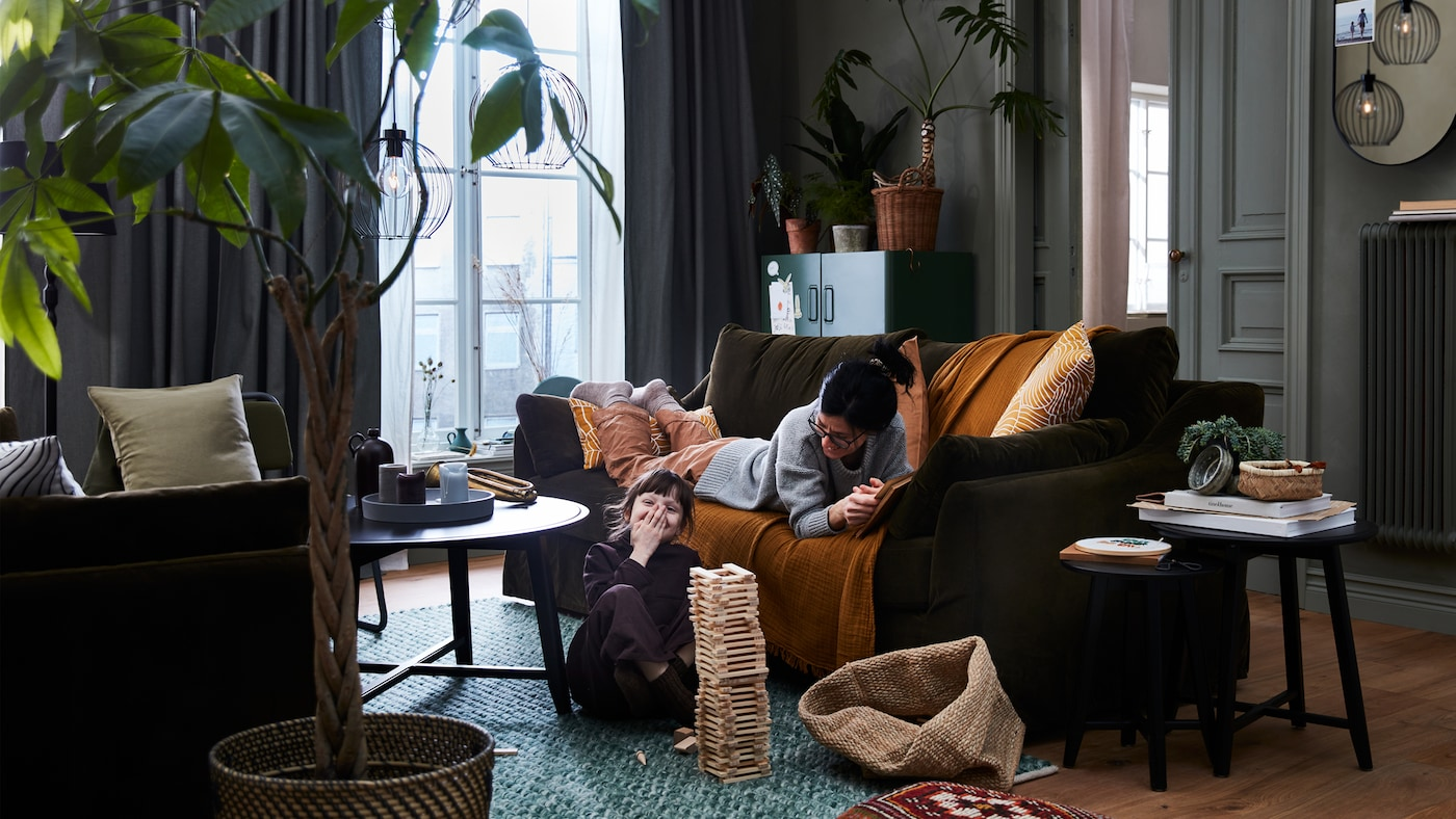 A mother on a FÄRLÖV sofa and a child on the floor play together. GRINDFALLET pendant lamps hang from the ceiling.