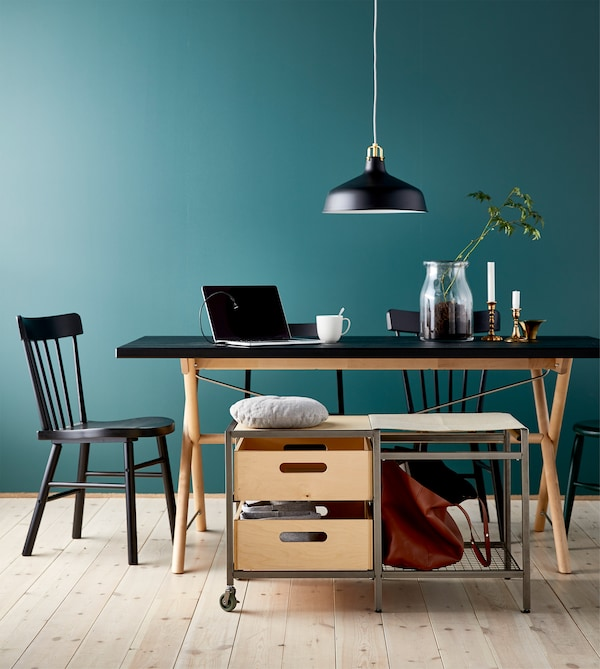 A movable storage bench with castors next to a large dining table that's being used as a study or work space.