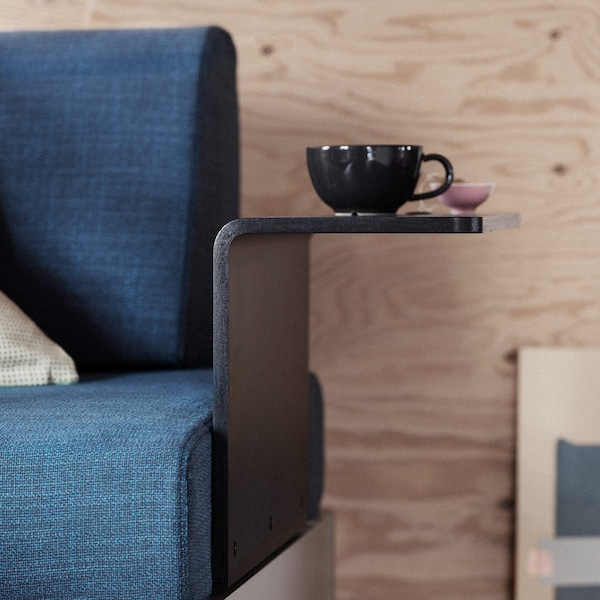 A mug on the side table of a dark blue DELAKTIG armchair.