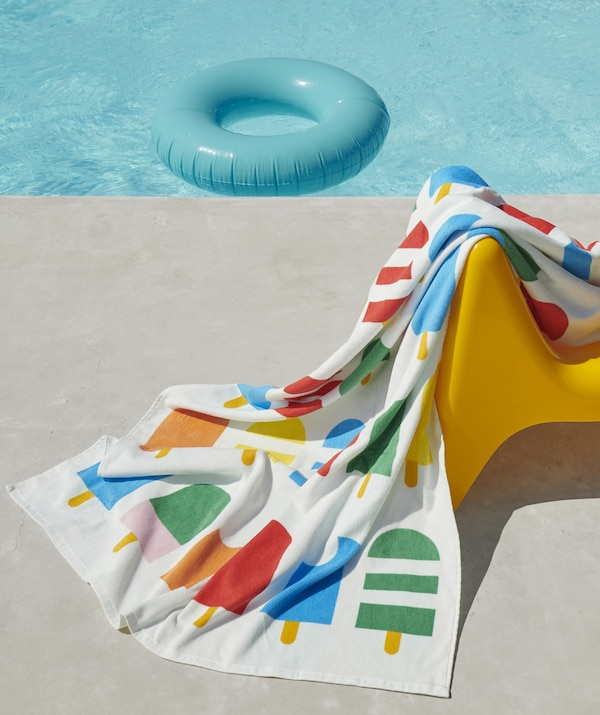 A multicolour towel with ice lolly print on a chair next to a swimming pool in the sunshine.