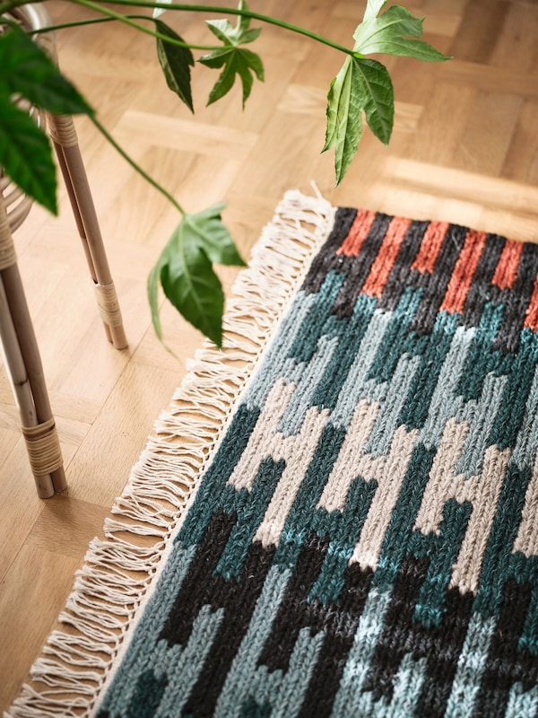 A multicoloured RESENSTAD rug sits next to a bamboo table with a green plant on top of it in a light room.