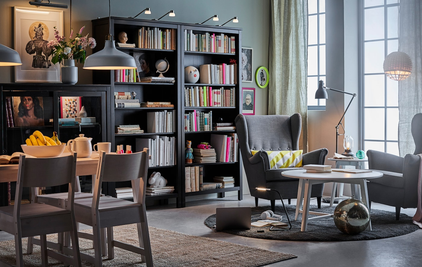 A multifunctional room with seating area, dining area, bookshelves and cabinets.