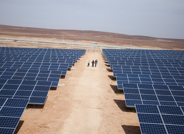 A multitude of solar panels mounted to the ground, situated in an arid plain.