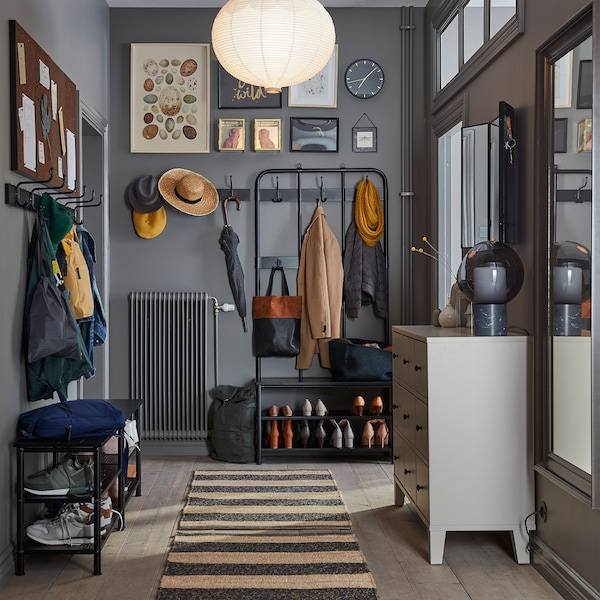 A narrow and grey hallway with a striped rug, a beige chest of drawers, a full-body mirror and benches with shoe storage.
