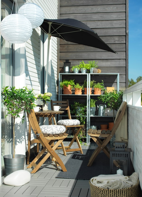 A narrow balcony with a wooden ASKHOLMEN table and chairs in the sun. Shelves with rows of plants can be seen behind.