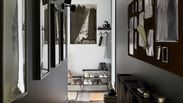 A narrow hallway with photos on the walls, black wired shoe storage stacked on top of each other, a black noticeboard.