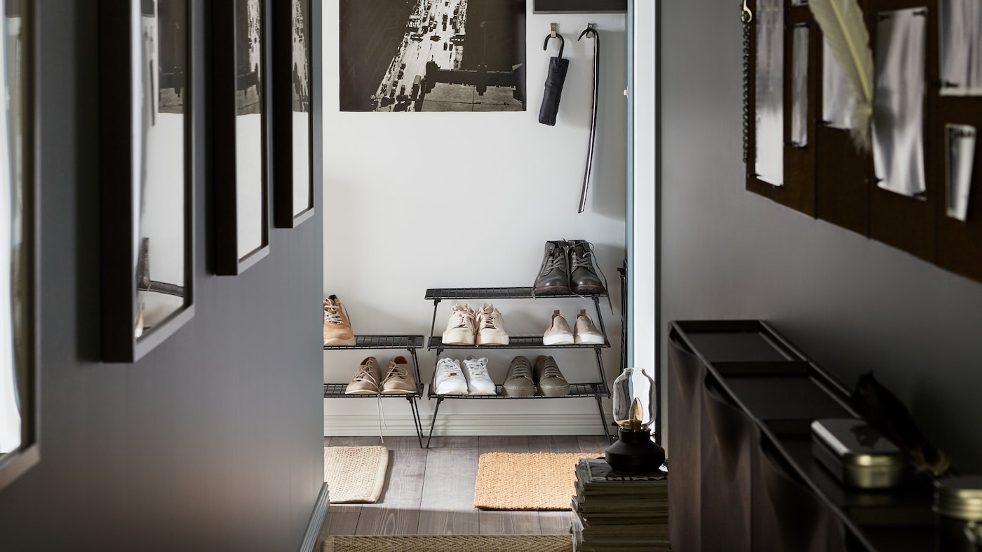 A narrow hallway with photos on the walls, steel GREJIG shoe racks stacked on top of each other and some SVENSÅS memo boards.