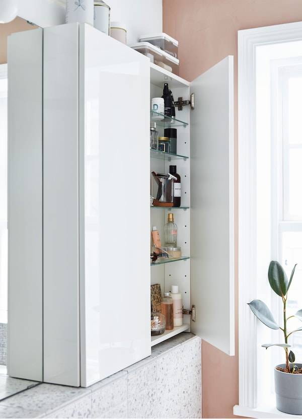 A narrow IKEA GODMORGON white wall cabinet, with glossy doors and 4 glass shelves stacked with bathroom supplies.
