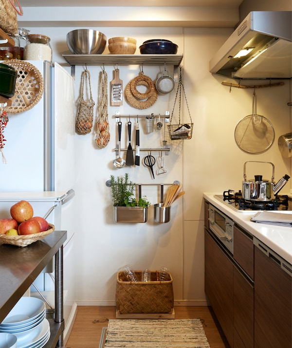A narrow kitchen with dark cabinets and utensils hanging on metal rails and shelves on the end wall.