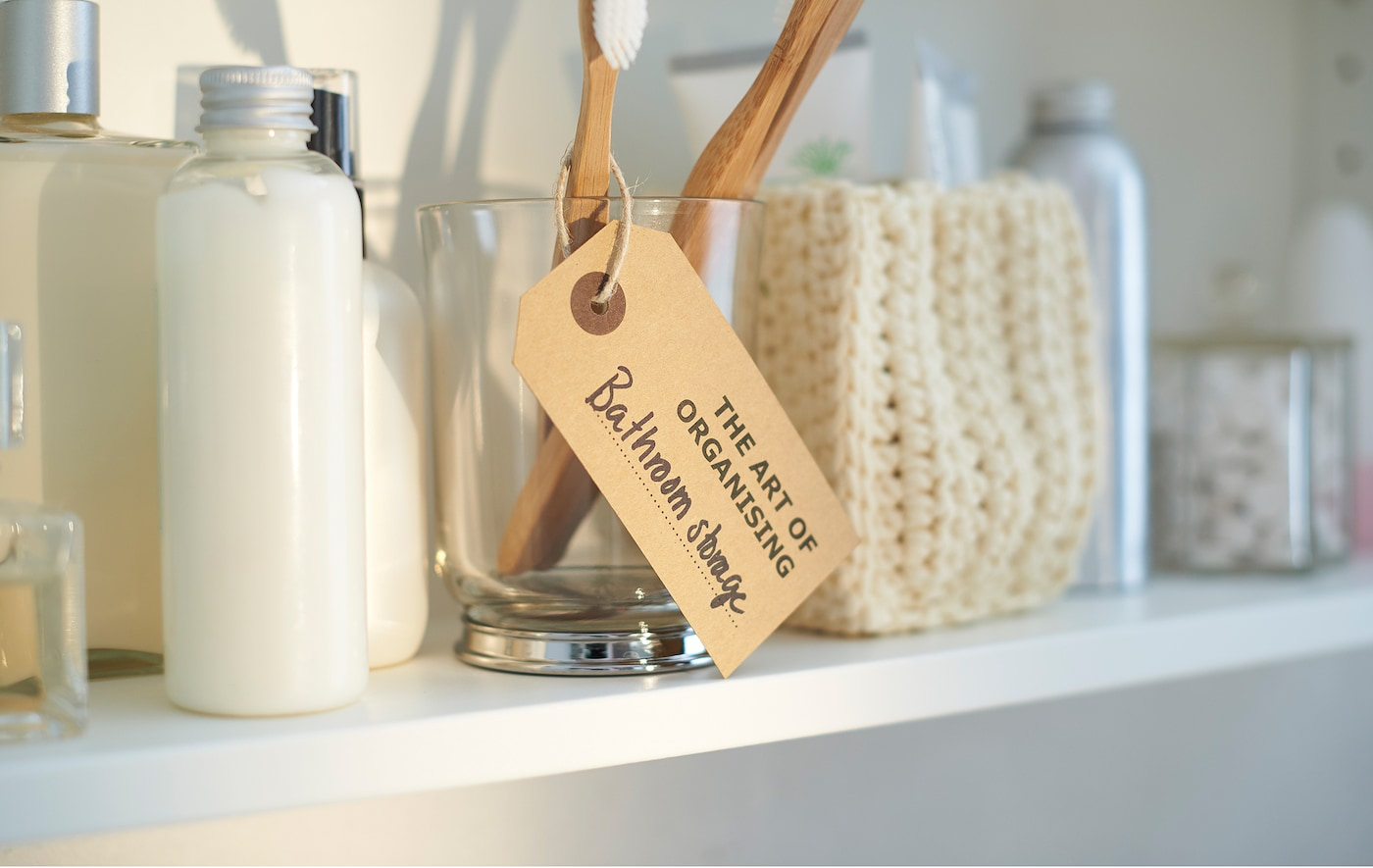 A neatly organised white bathroom shelf with bottles, a woven basket, and a clear glass holding a toothbrush.