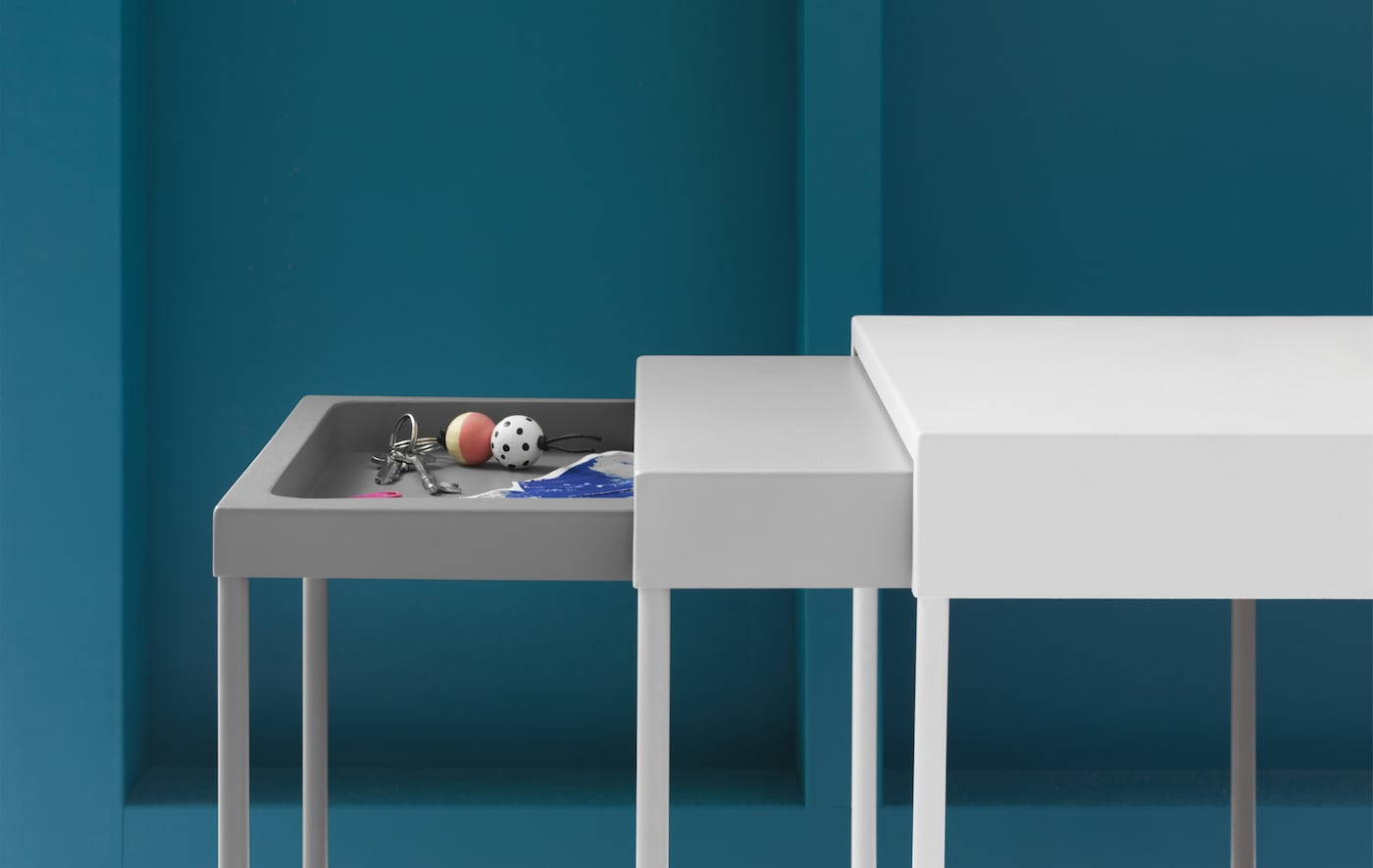 A nest of three tables with a tray in the top of the smallest table.