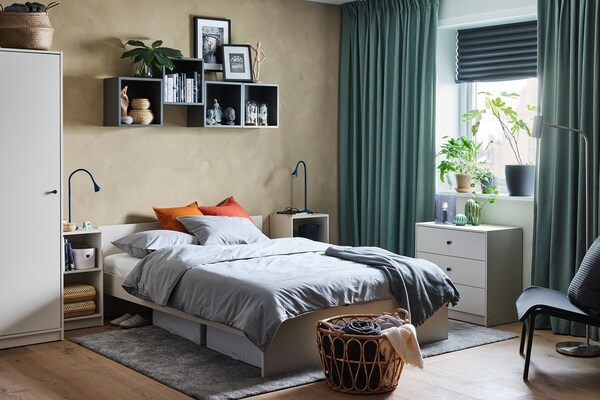A neutral bedroom with a white MALM bed with storage underneath. There is a cube shaped bedside table on each side of the bed, each with a blue lamp on top and other decorative accessories.