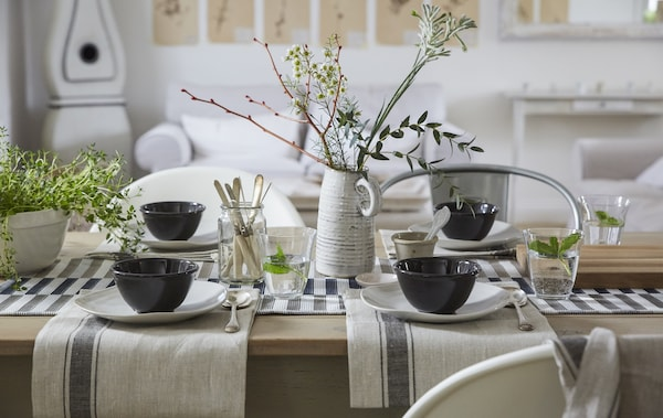 A neutral-colored table setting with cotton napkins, simple place settings and a natural centrepiece.