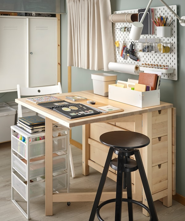 A NORDEN table arranged for scrapbooking, highly organised and accessories within reach on table, pegboard and in drawers.