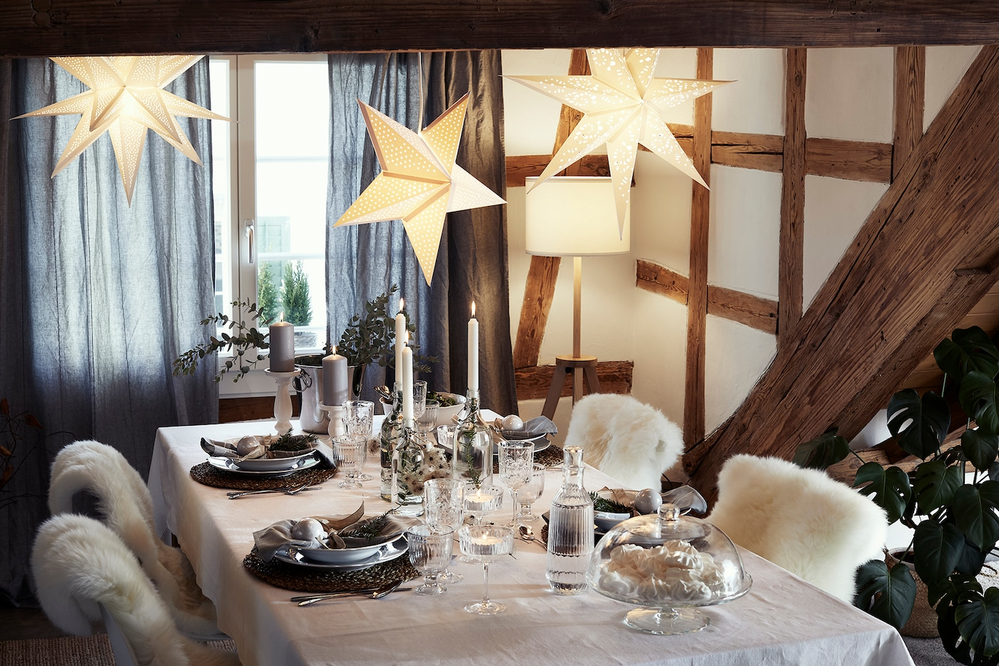 A Nordic winter inspired table decoration, with rustic placemats, candles, and sheepskin.