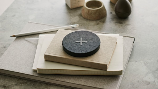 A NORDMÄRKE wireless charger with a big plus symbol on its grey textile cover, placed on top of a pile of books on a table.