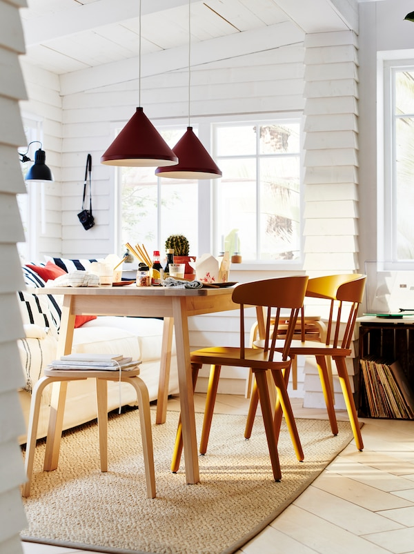 A NORRÅKER table surrounded by OMTÄNKSAM chairs, forming a dining set in a white, sunlit room lined with clapboard walls.