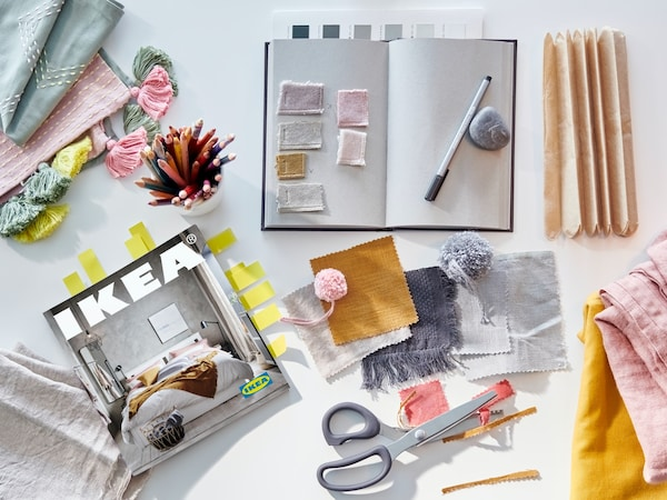 A note book, a pen, scissors, and pieces of fabric in pink, grey, yellow, mustard, and green beside a 2021 IKEA Catalogue.