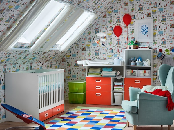 A nursery decorated with patterned wallpaper and white STUVA FRITIDS cot with two red drawers, changing table and bookcase.