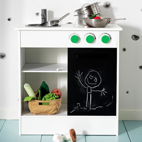 A NYBAKAD play kitchen with a sliding blackboard door with pots and pans on the top and a basket of play vegetables below.