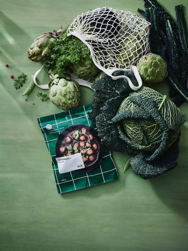 A pack of HUVUDROLL plant balls lies on a green fabric surface with an assortment of vegetables above it.