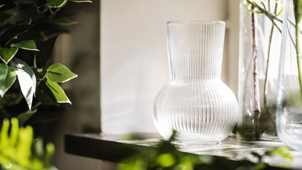 A PÅDRAG vase by a windowsill with plants surrounding it.