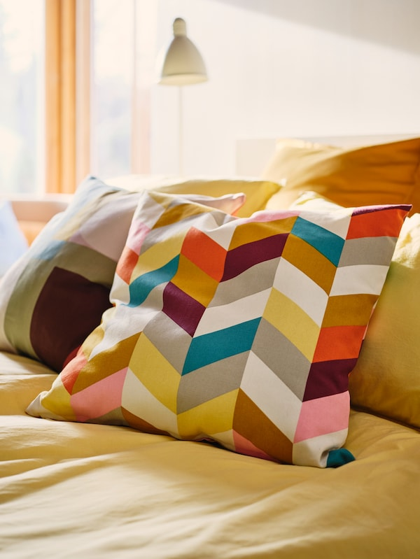 A pair of cushions, enveloped in HANNELISE and STENMÄTARE cushion covers, lie atop a bright yellow bedcover in a bedroom.