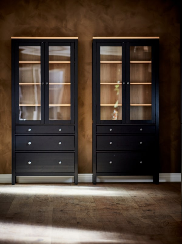 A pair of dark HEMNES glass-door cabinets standing empty against the brown wall of an otherwise empty room.