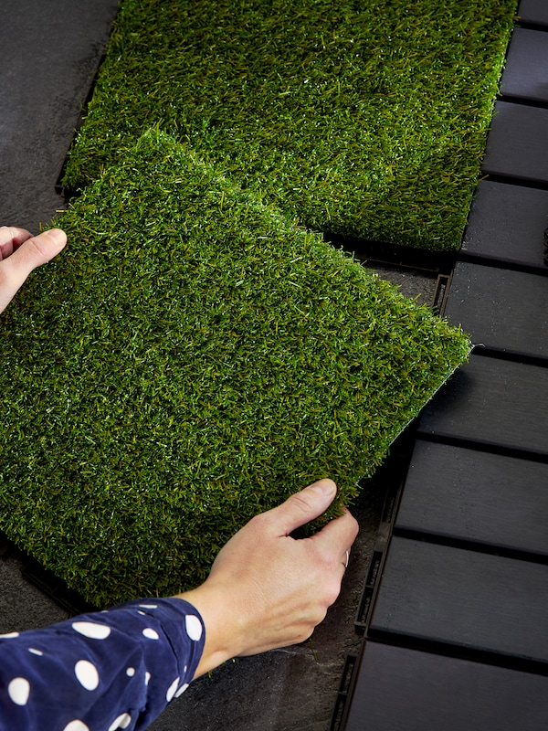 A pair of hands holding some floorcovering that looks like grass turf, above a wooden floor of dark brown wooden slats.