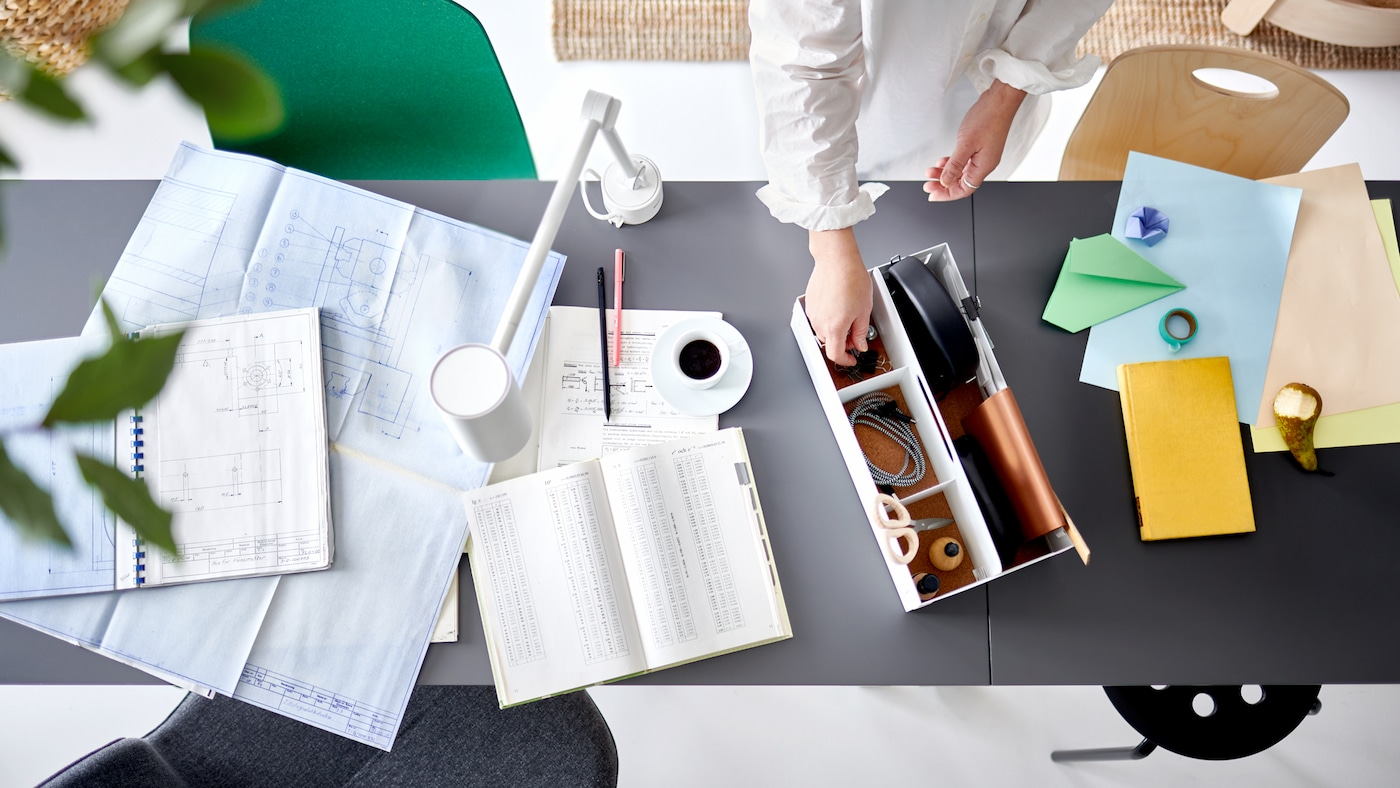 A pair of hands picking an item from a white desk organiser on two joined table tops with work papers and a white work lamp.
