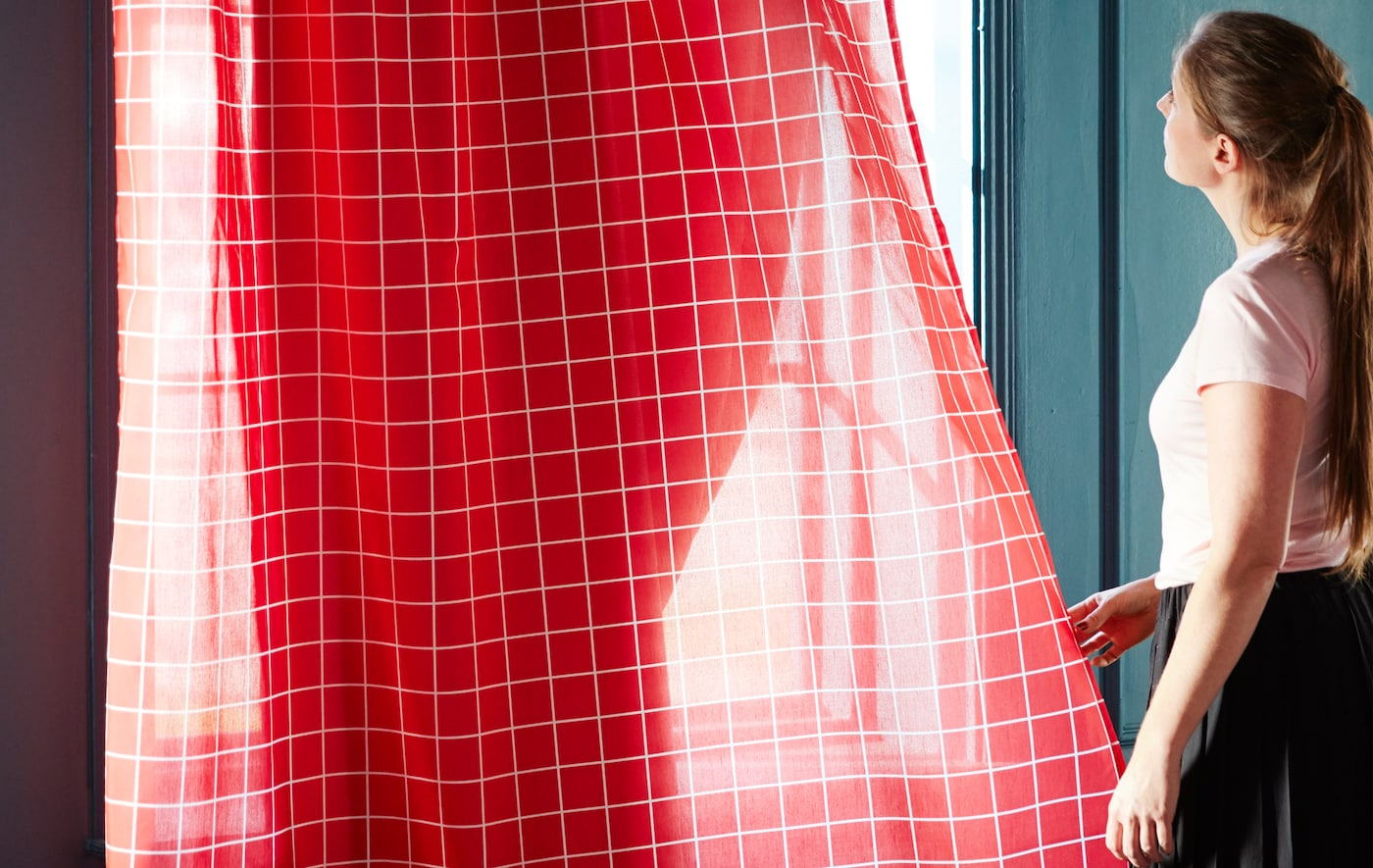 A pair of sheer IKEA ROSALILL curtains with white lines on a red background are letting some sunshine into a room.