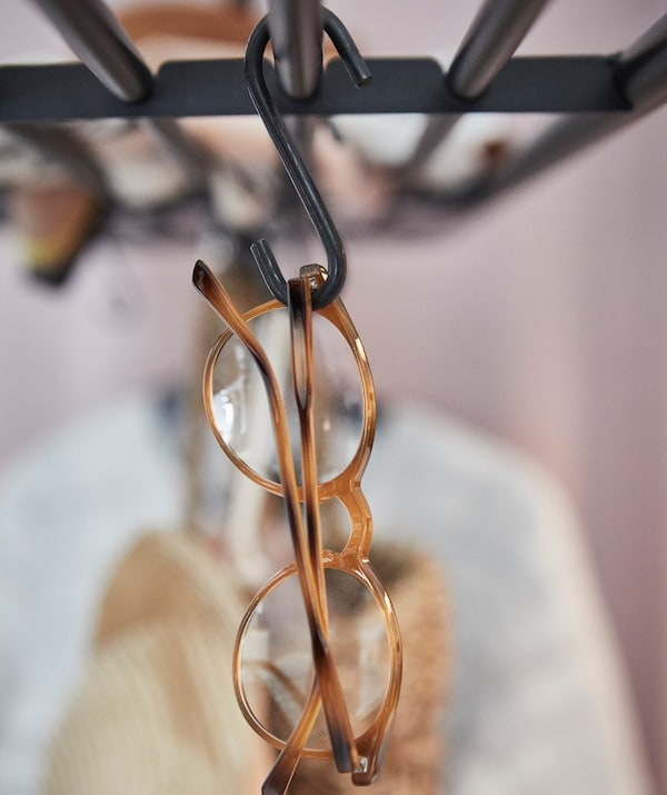 A pair of spectacles hanging on a VADHOLMA rack.