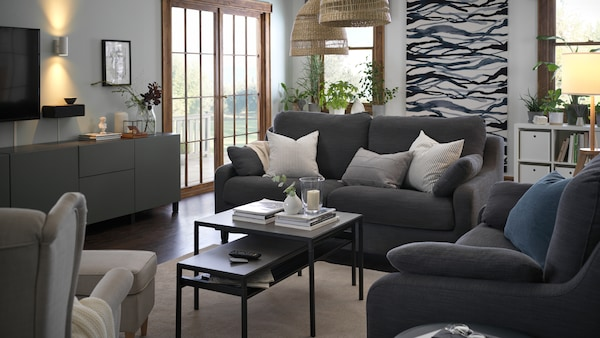 A pair of VINLIDEN three-seat sofas at ninety degrees with two NYBODA nesting tables, black, in between.