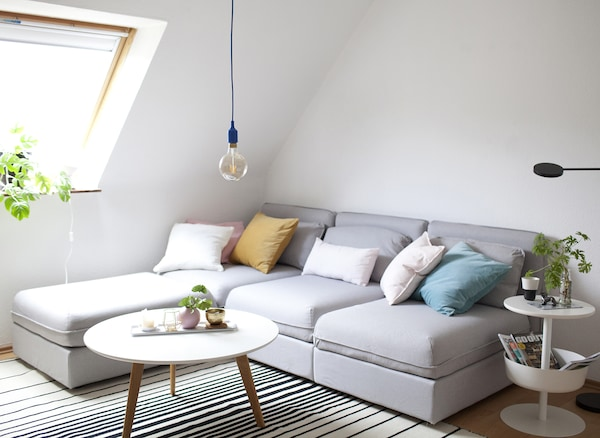 A pale grey corner sofa, striped rug, coffee table and side table with storage.