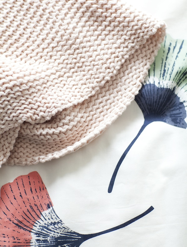 A pale pink throw on top of a bed cover.